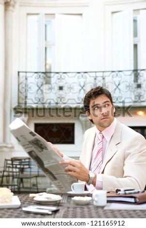 Attractive young businessman reading the newspaper while having breakfast at a coffee shop near classic office buildings in the city. - stock photo