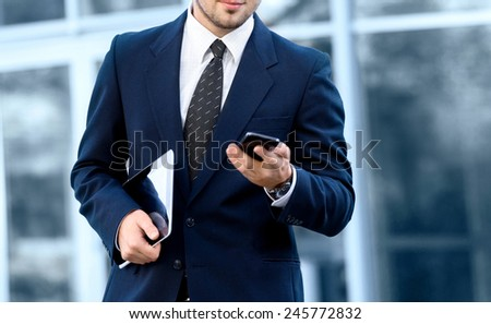 Attractive young businessman using a cell phone, smiling. Taken in front of a modern office building. - stock photo