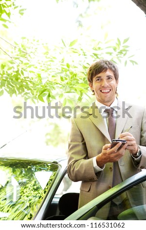 Attractive young businessman using a digital tablet while leaning on the door of his car in a classic city street, smiling. - stock photo