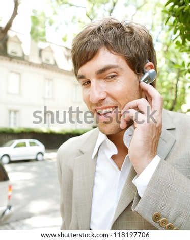Attractive young businessman using a hands free ear piece device to make a phone call while in a classic city financial district, outdoors. - stock photo