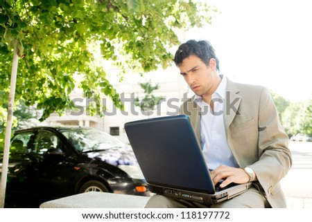 Attractive young businessman using a laptop computer while sitting on a bench in the financial district of a classic city, working outdoors. - stock photo