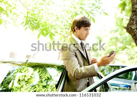 Attractive young businessman using a smart phone while leaning on the door of his car in a classic city street. - stock photo
