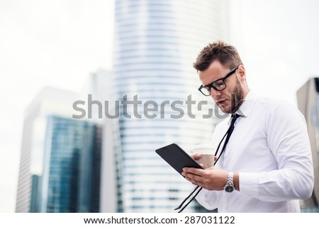 Attractive young businessman using a tablet and drinking coffee. Standing in front of a modern office building. - stock photo
