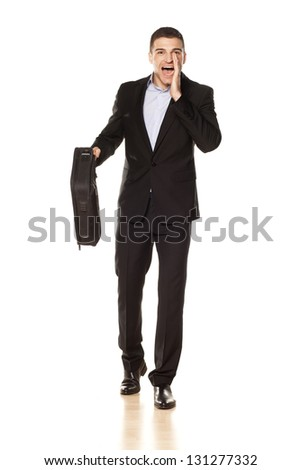 attractive young businessman with a laptop bag, shouting with his hand next to his mouth