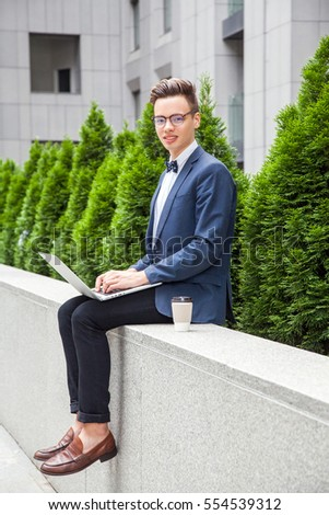 Attractive young businessman with laptop and coffee in hands on office building background. holding laptop and looking at camera with toothy smile.