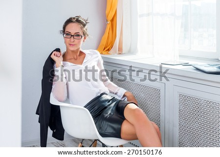 Attractive young businesswoman in glasses sitting on the white chair next to the window with the jacket in her hands - stock photo