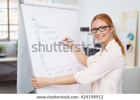 Attractive young businesswoman preparing a presentation writing notes on a flip chart in the office turning to smile at the camera - stock photo