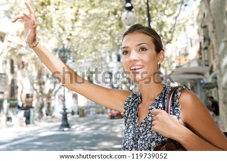 Attractive young businesswoman raising her arm to call a taxi in a busy city, outdoors. - stock photo