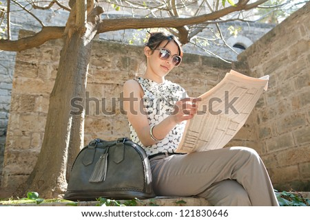 Attractive young businesswoman reading a financial newspaper while sitting down on a stone wall in a park on a sunny day.