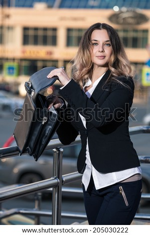 Attractive young businesswoman, sorting briefcase