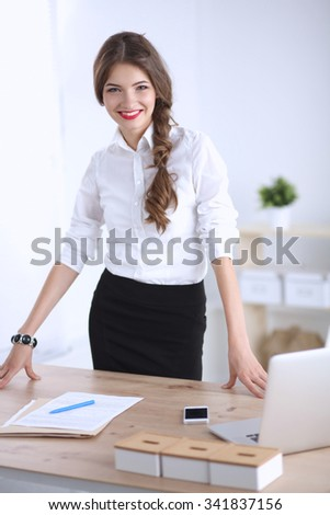 Attractive young businesswoman standing  near desk in office - stock photo