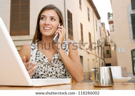 Attractive young businesswoman using a cell phone to make a call while using a laptop computer, sitting at a coffee shop terrace outdoors, smiling.