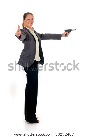 Attractive young businesswoman with gun, weapon.  studio shot.
