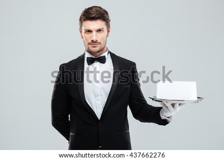 Attractive young butler in tuxedo and gloves holding tray with blank card - stock photo