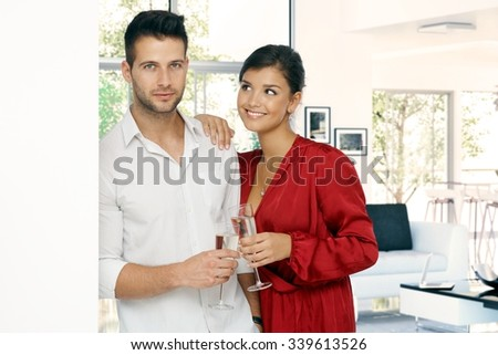 Attractive young casual romantic couple at home with champagne glass in hand. Standing, leaning against wall. Handsome man and attractive woman in red dressing gown, smiling. - stock photo