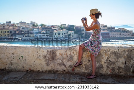 Attractive young Caucasian brunette woman in casual dress photographing during holidays in Greece - stock photo