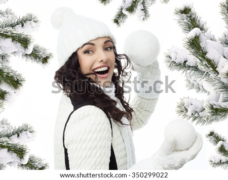 attractive young caucasian woman in warm clothing  smiling christmas tree covered with snow