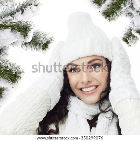 attractive young caucasian woman in warm clothing  smiling christmas tree covered with snow - stock photo
