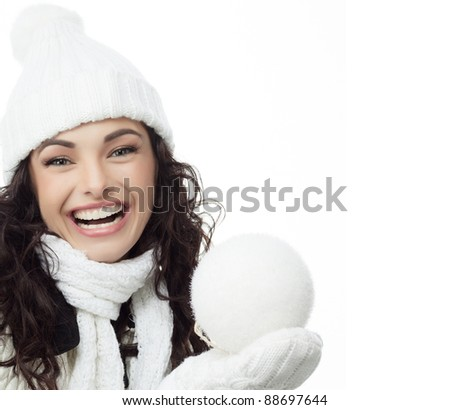 attractive young caucasian woman in warm clothing  smiling with snowball - stock photo