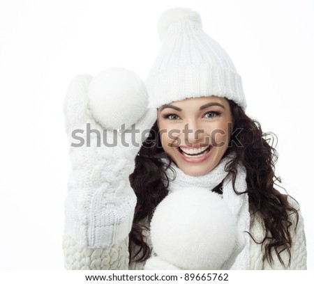 attractive young caucasian woman in warm  clothing  smiling with snowball