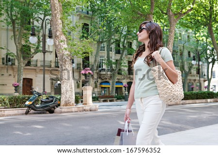Attractive young consumer woman walking down a large avenue with elegant buildings and trees, carrying paper shopping bags during a fun and sunny day, outdoors. - stock photo
