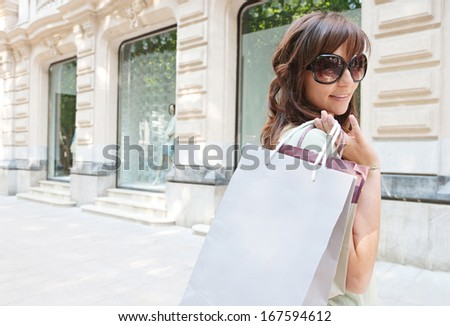 Attractive young consumer woman walking down a shopping avenue with elegant buildings and stores, carrying paper bags during a fun and sunny day, turning to smile at the camera. - stock photo