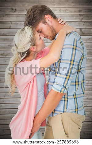Attractive young couple about to kiss against wooden planks background - stock photo