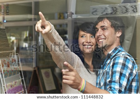 Attractive young couple agree and point at item in shop window - stock photo
