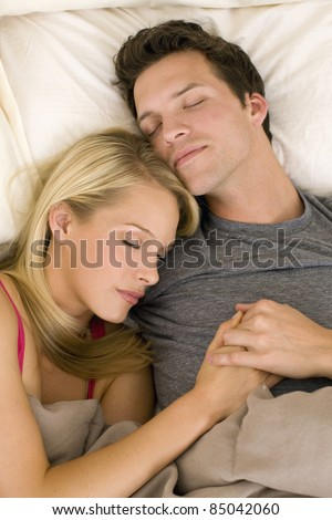 Attractive young couple asleep in bed - stock photo