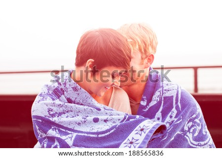 Attractive Young Couple at Sunset sitting in a truck bed at the beach in California - stock photo