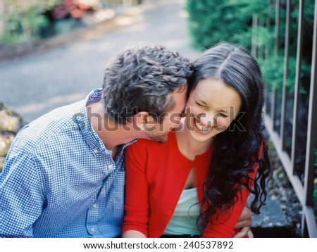 Attractive Young Couple Blurry Shot of Movement man nuzzling into girls neck, laughing - stock photo