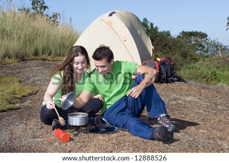 Attractive young couple cooking a meal while on a camping trip. Horizontally framed shot set against a clear blue sky - stock photo