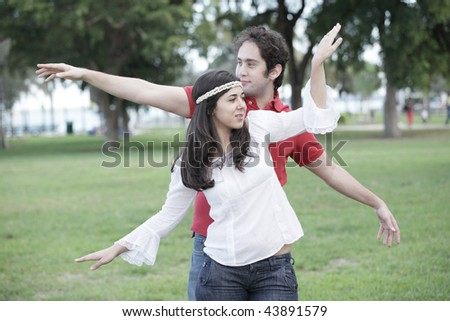 Attractive young couple dancing in the park - stock photo
