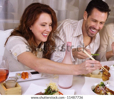 Attractive young couple eating sushi. - stock photo