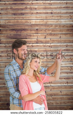 Attractive young couple embracing and pointing against wooden planks - stock photo