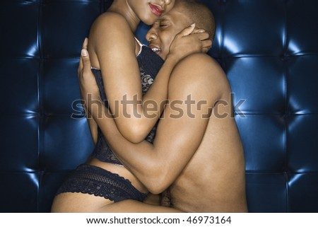 Attractive young couple embracing. The man is shirtless and the woman is wearing sexy lingerie. Horizontal shot.