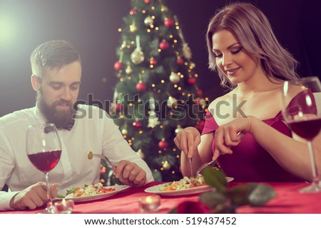 Attractive young couple enjoying a romantic Christmas dinner. Focus on the girl