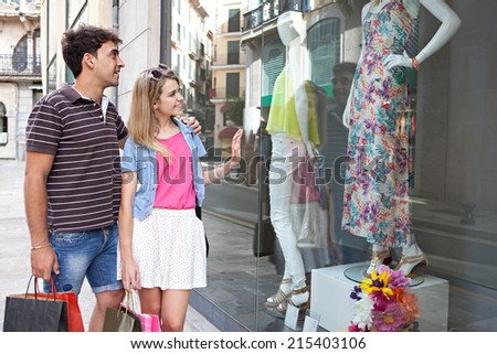 Attractive young couple enjoying a vacation city break together, looking at the fashion store shop windows smiling while shopping, outdoors. Consumer and travel lifestyle. - stock photo