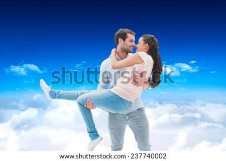 Attractive young couple having fun against bright blue sky over clouds - stock photo