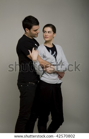 Attractive young couple having fun against grey background