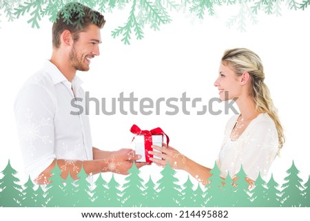 Attractive young couple holding a gift against frost and fir trees in green - stock photo