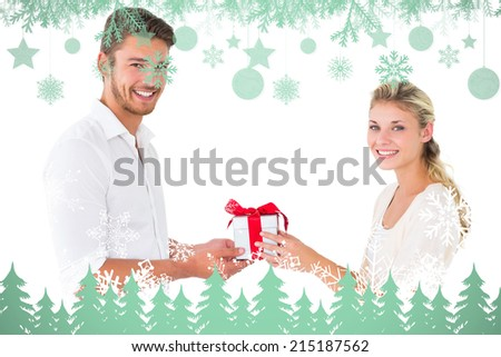 Attractive young couple holding a gift against snowflakes and fir trees in green - stock photo