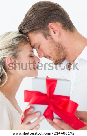 Attractive young couple holding gift over white background - stock photo