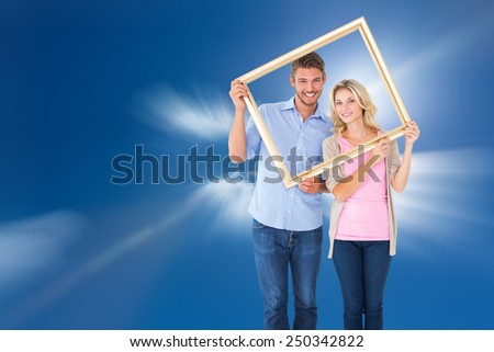 Attractive young couple holding picture frame against bright blue sky with clouds - stock photo