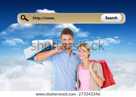 Attractive young couple holding shopping bags against bright blue sky with clouds - stock photo