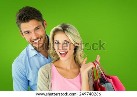 Attractive young couple holding shopping bags against green vignette - stock photo