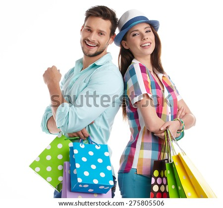 Attractive young couple holding shopping bags on white background