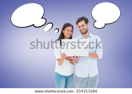 Attractive young couple holding their laptop against purple vignette - stock photo