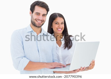 Attractive young couple holding their laptop on white background - stock photo