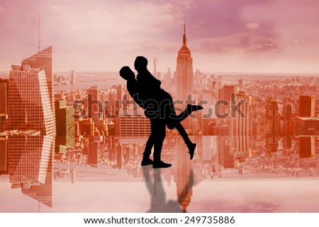 Attractive young couple hugging each other against room with large window looking on city - stock photo